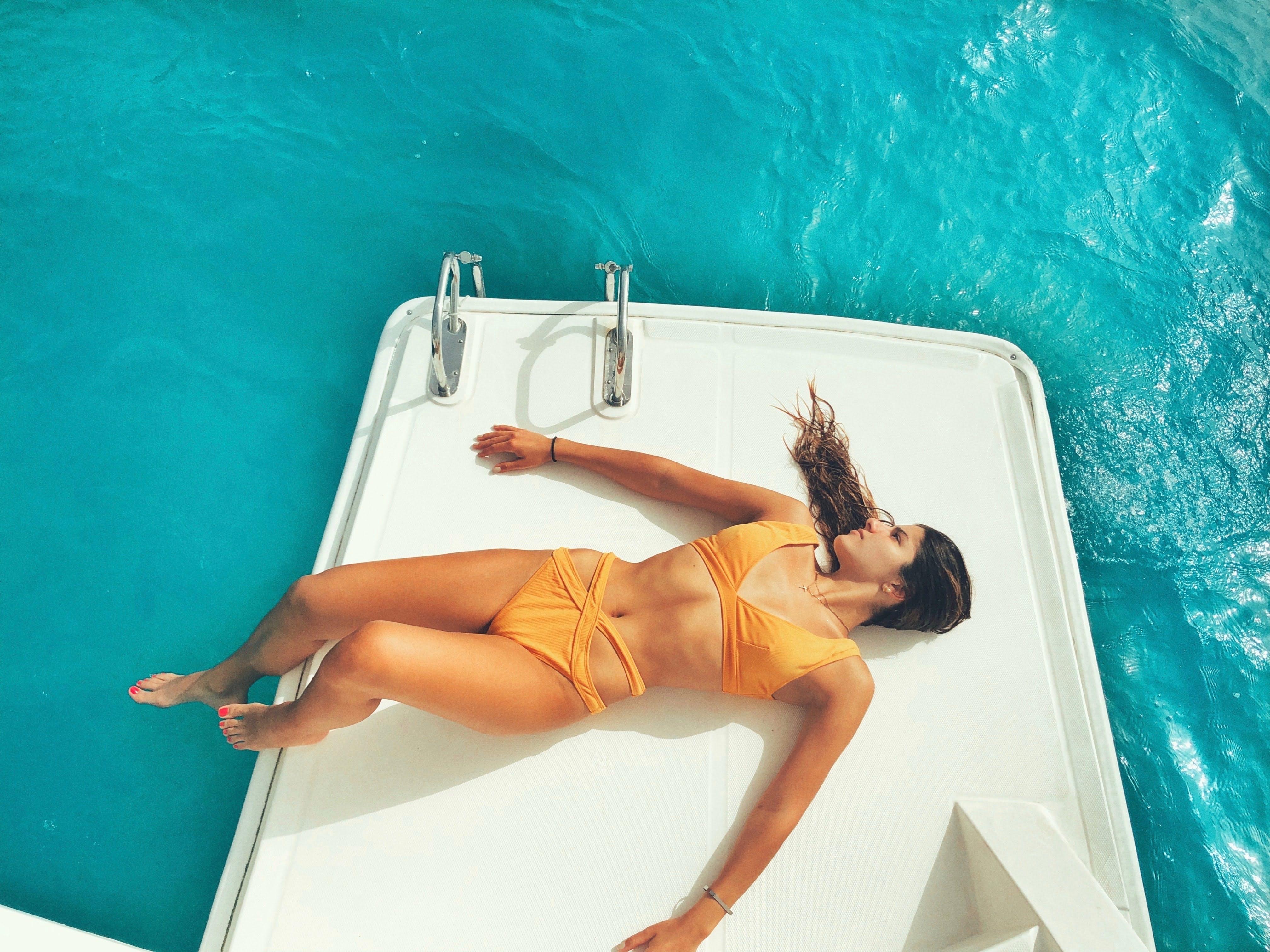 Tjej i badkläder som solar på en brygga