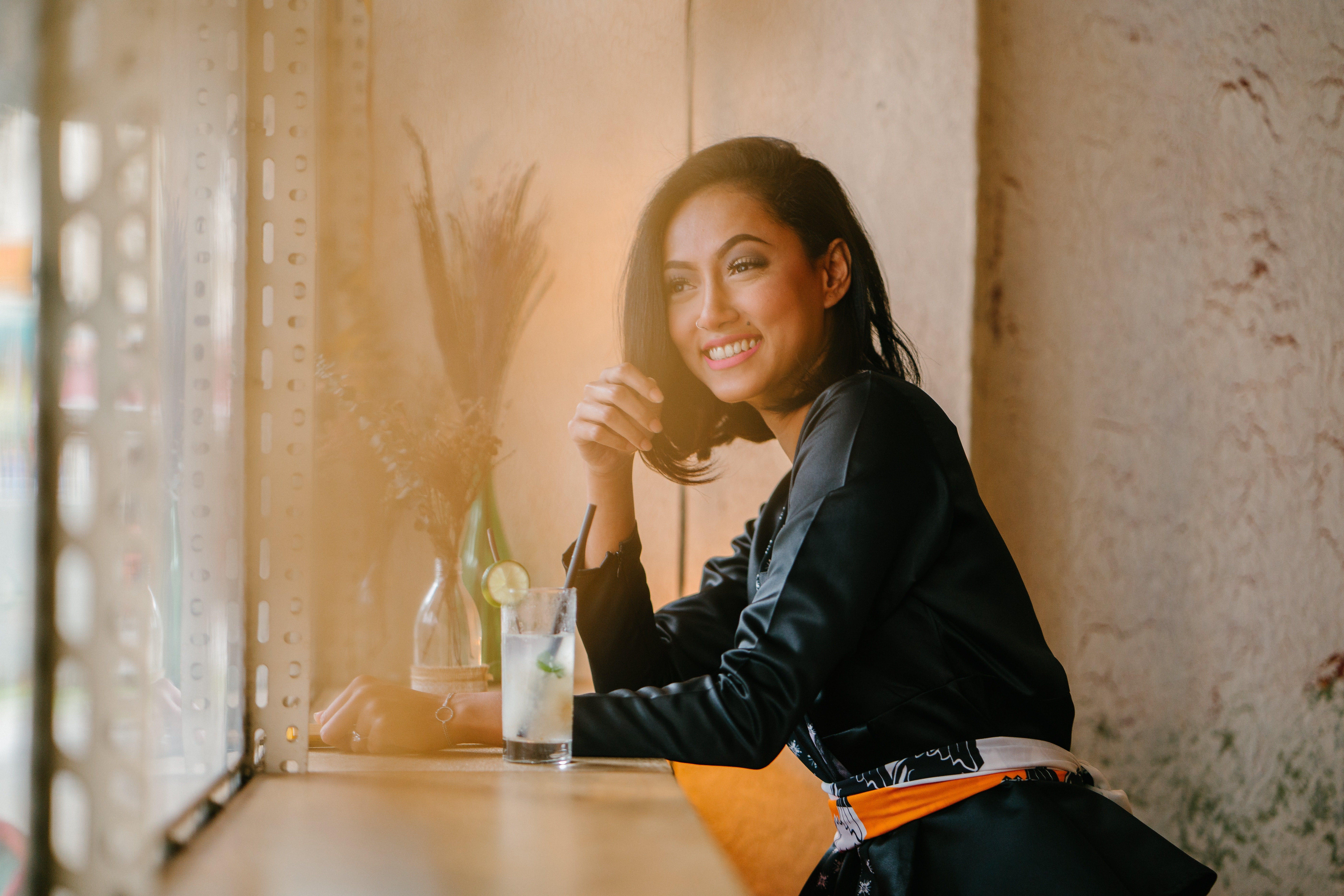 Tjej i mörka kläder sitter på ett cafe med en drink