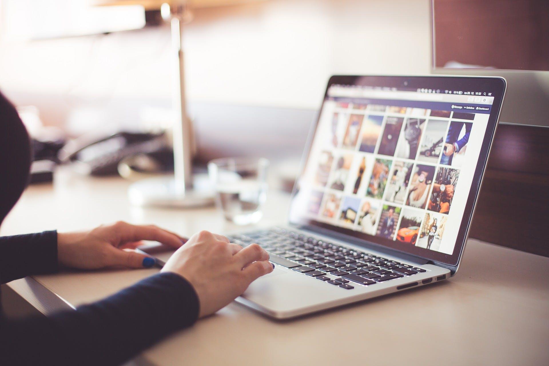 Kvinna som sitter och kollar bilder på en dator i ett kontor