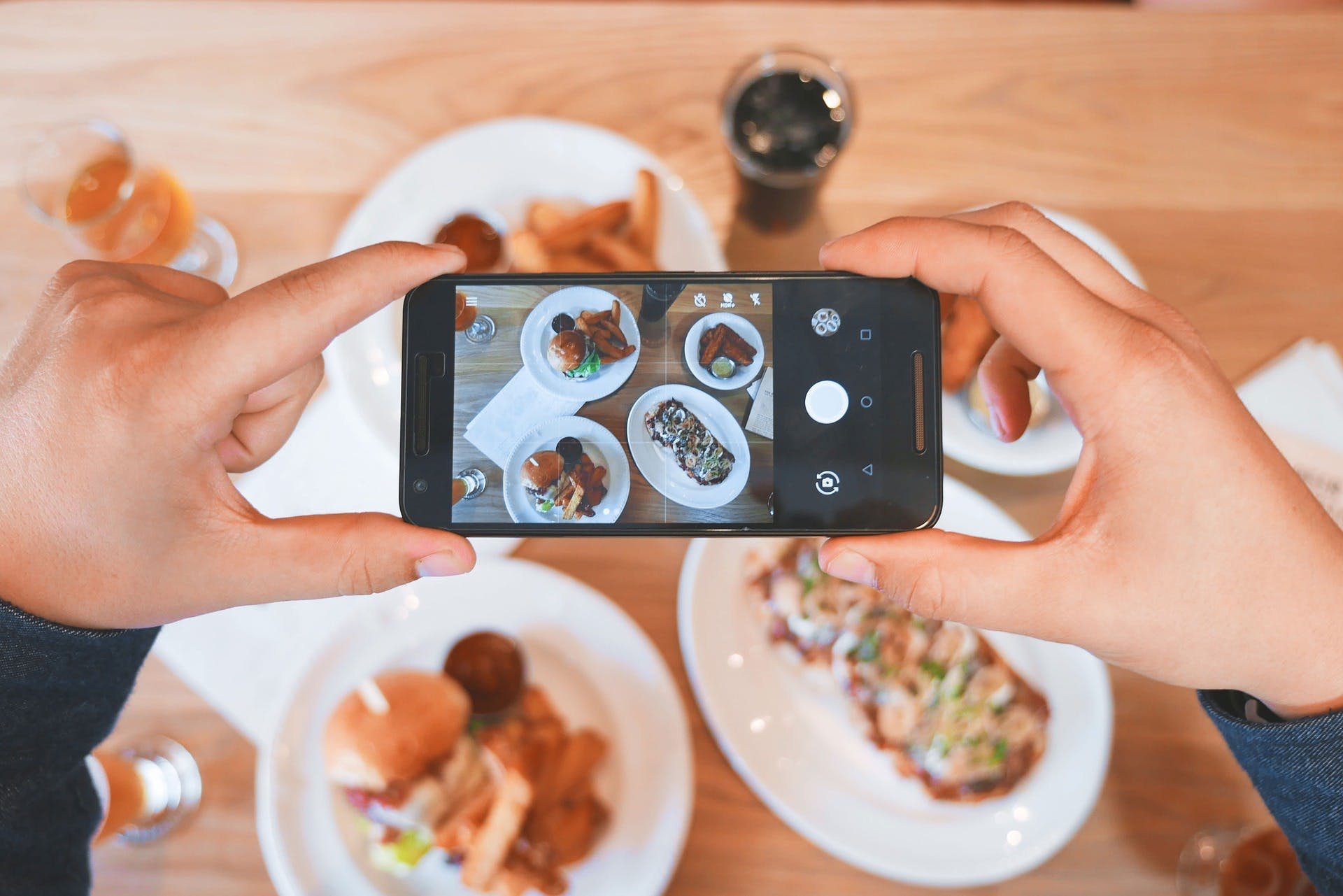 Person holding a phone and taking a picture of their food