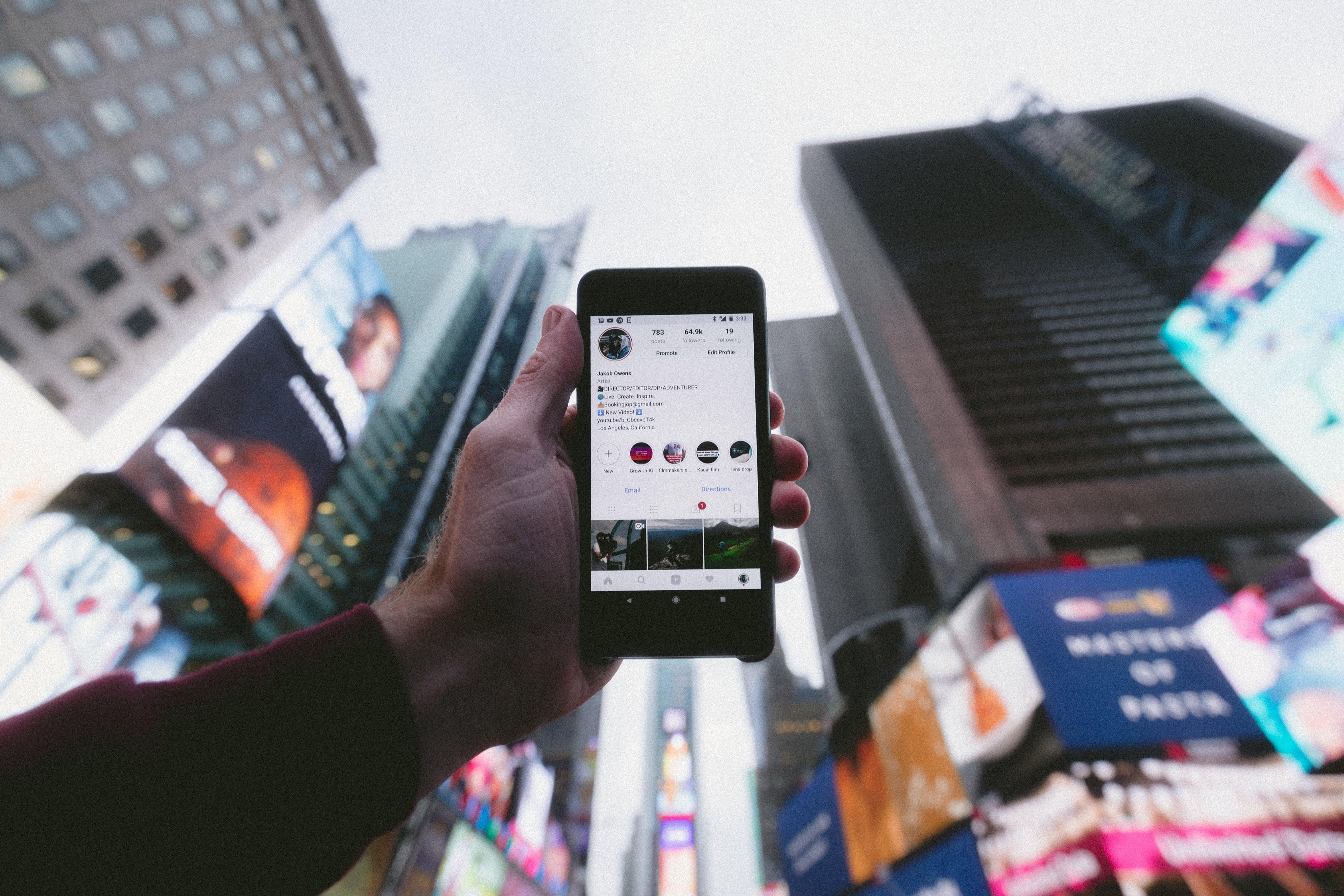 Person som håller i en mobil mot himlen i en storstad och mobilen visar ett instagramkonto