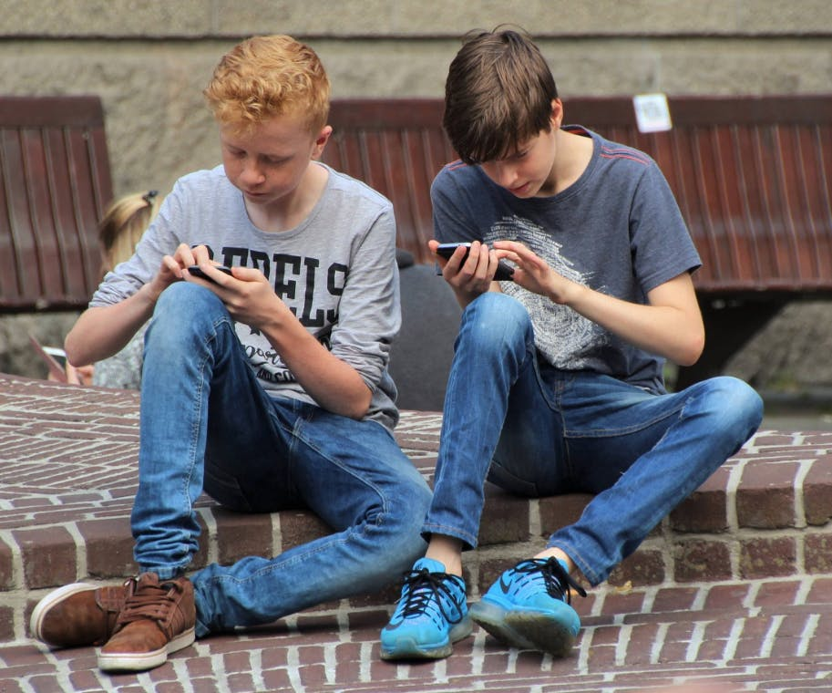 Two teen boys looking at their phones and interacting with it