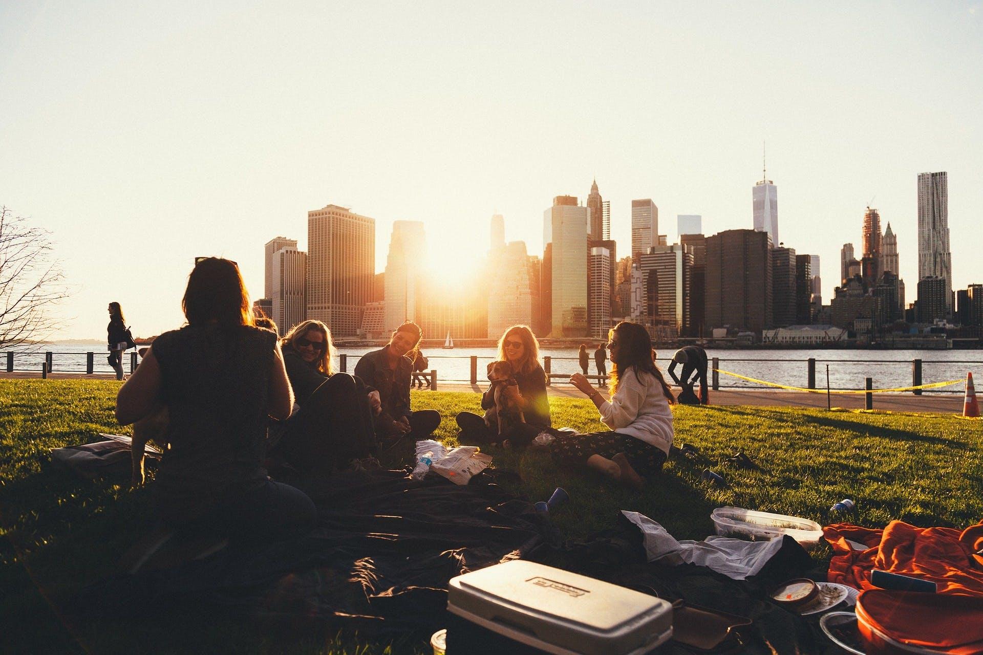 En grupp med människor sitter i en park i solnedgången med New York i bakgrunden