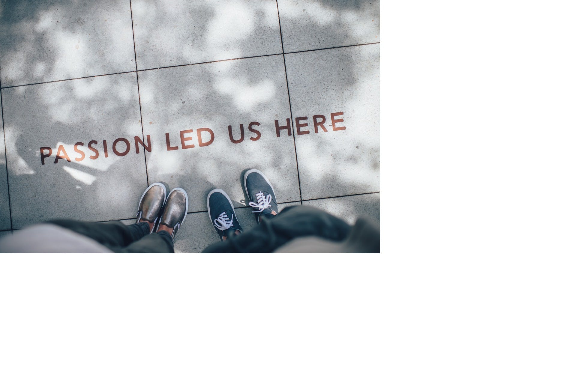 Två personer står på en väg och framför dem på vägen står det: passion led us here