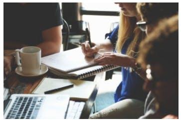 En grupp med personer som sitter vid ett bord och gör anteckningar och jobbar på sin macbook