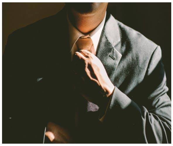 Man i kostym som rättar till sin slips